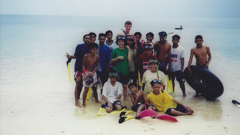 An American male stands with teenage Filipino students in clear blue waters.