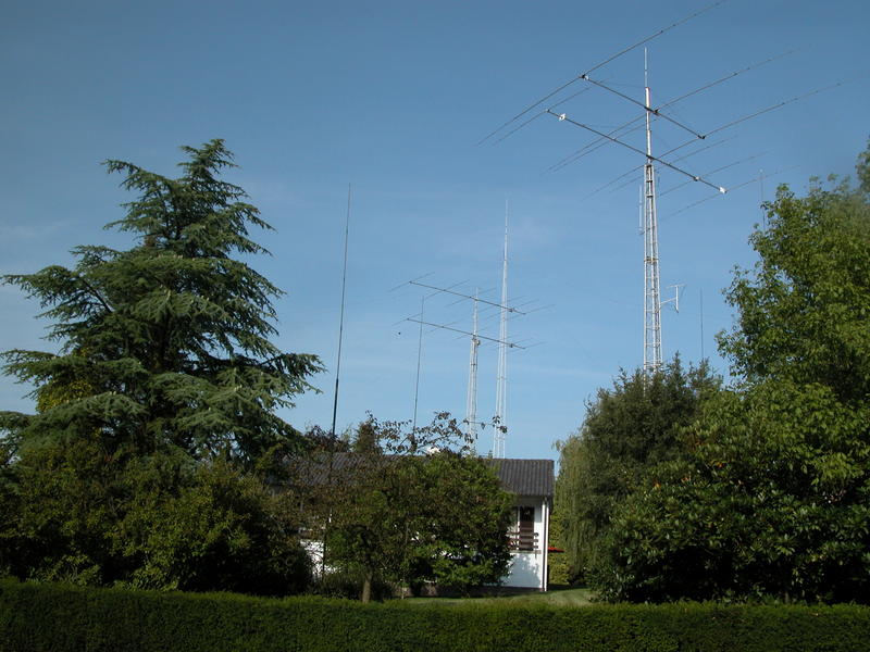 View from the street of the towers with the single band home-made yagis at ON4UN, as well as the 160m quarter-wave vertical.
