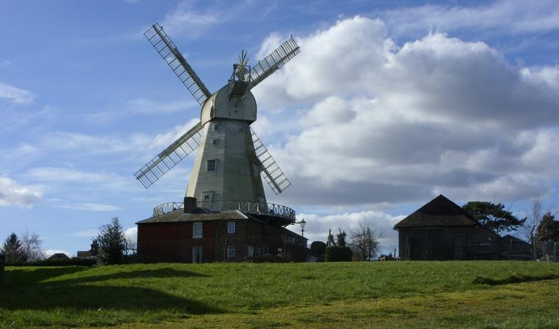 White Kentish Smock Mill against a blue sky with white clouds