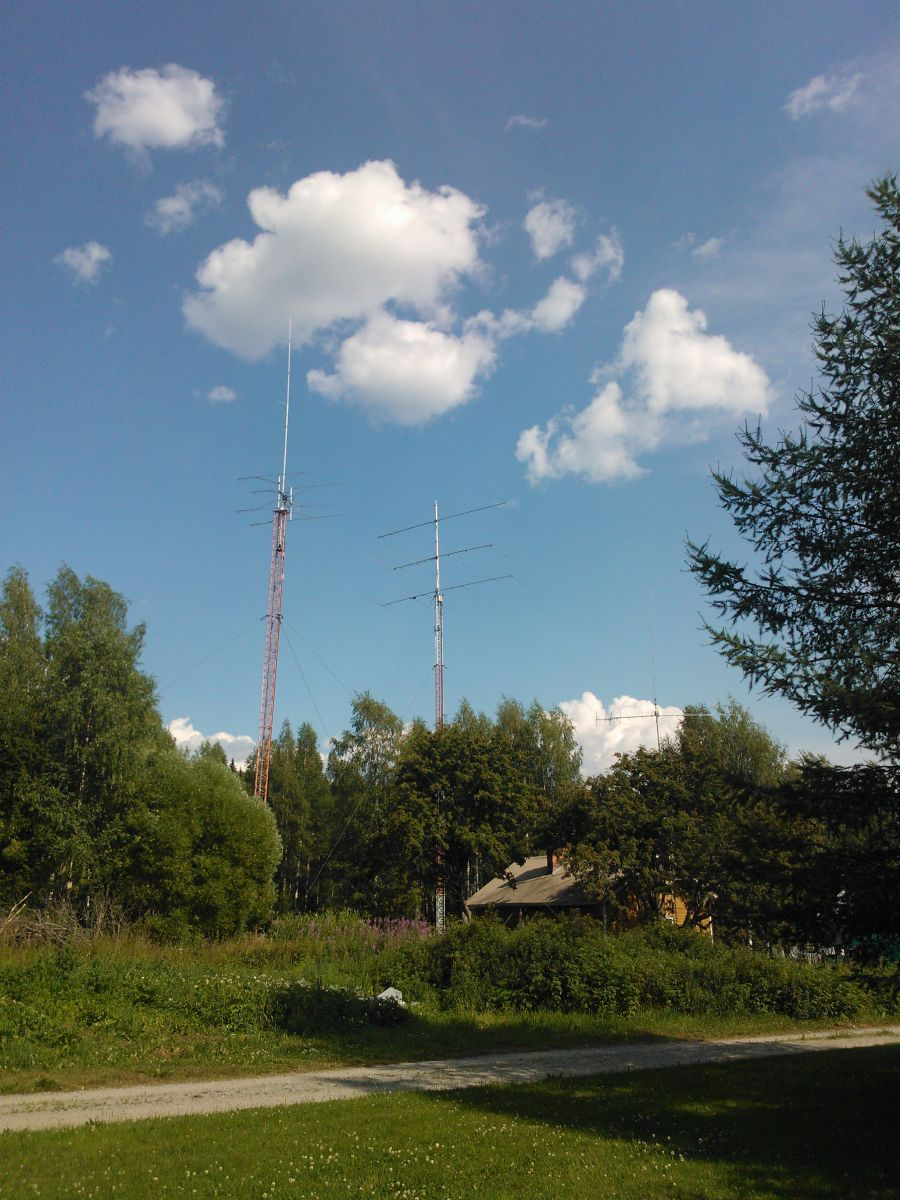 Collection of antennas: Left mast 4x70cm yagis and dualband vertical. Right mast from up 6m yagi, cushcraft X9 and dualband yagi for warc 17&12m