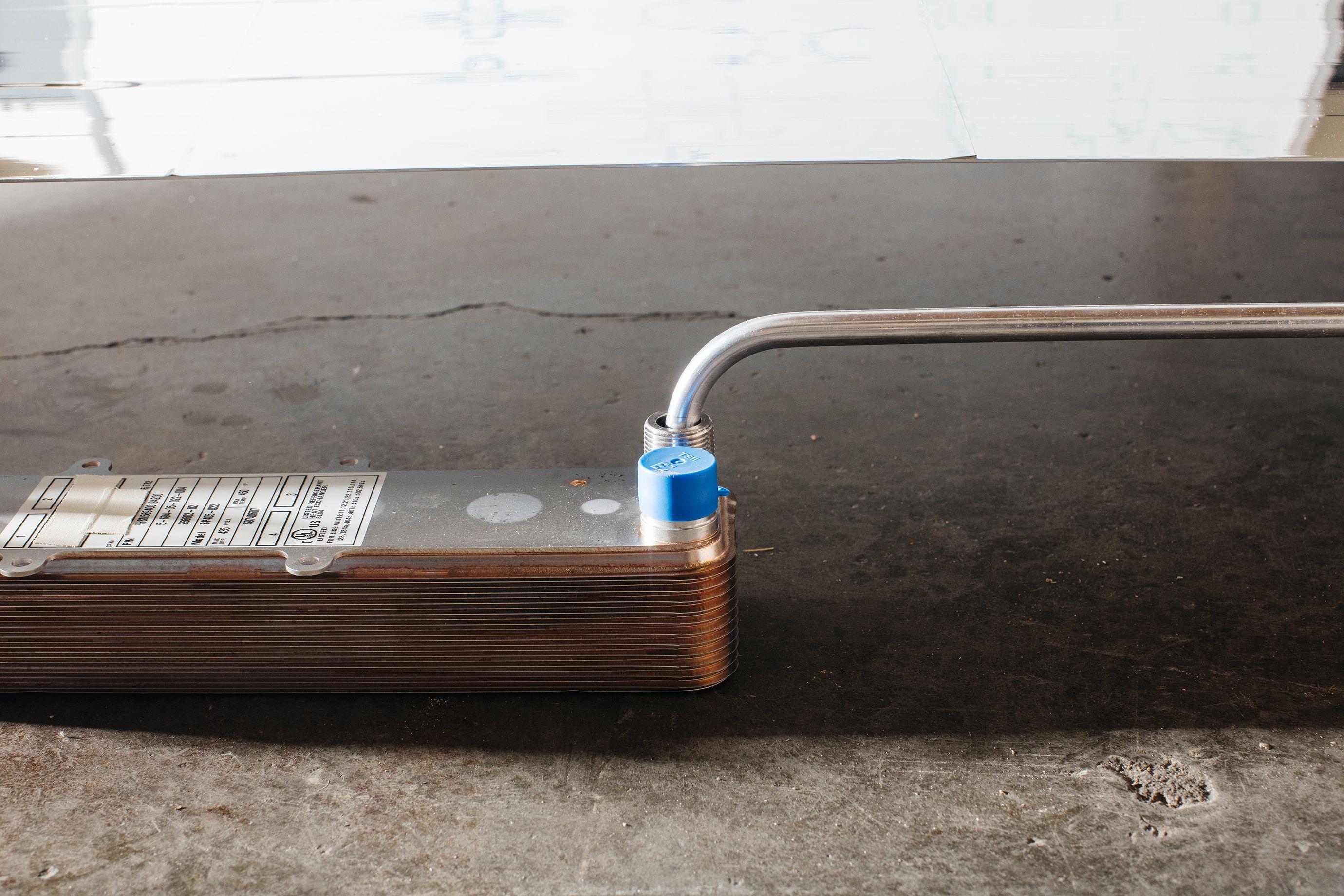 El calor del refrigerante se transfiere a la mezcla de agua a través de placas de metal dentro del intercambiador de calor. El líquido calentado sale del intercambiador de calor a través de tuberías.
