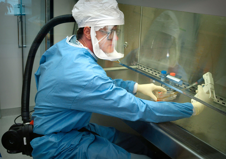 Un microbiólogo del personal de los CDC examina un virus de influenza pandémica de 1918 reconstruido.