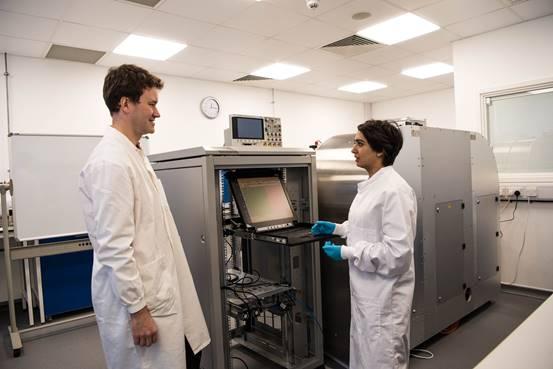 Los investigadores se ubican frente a un prototipo parcialmente completado de una máquina de almacenamiento de datos de ADN en Boston.