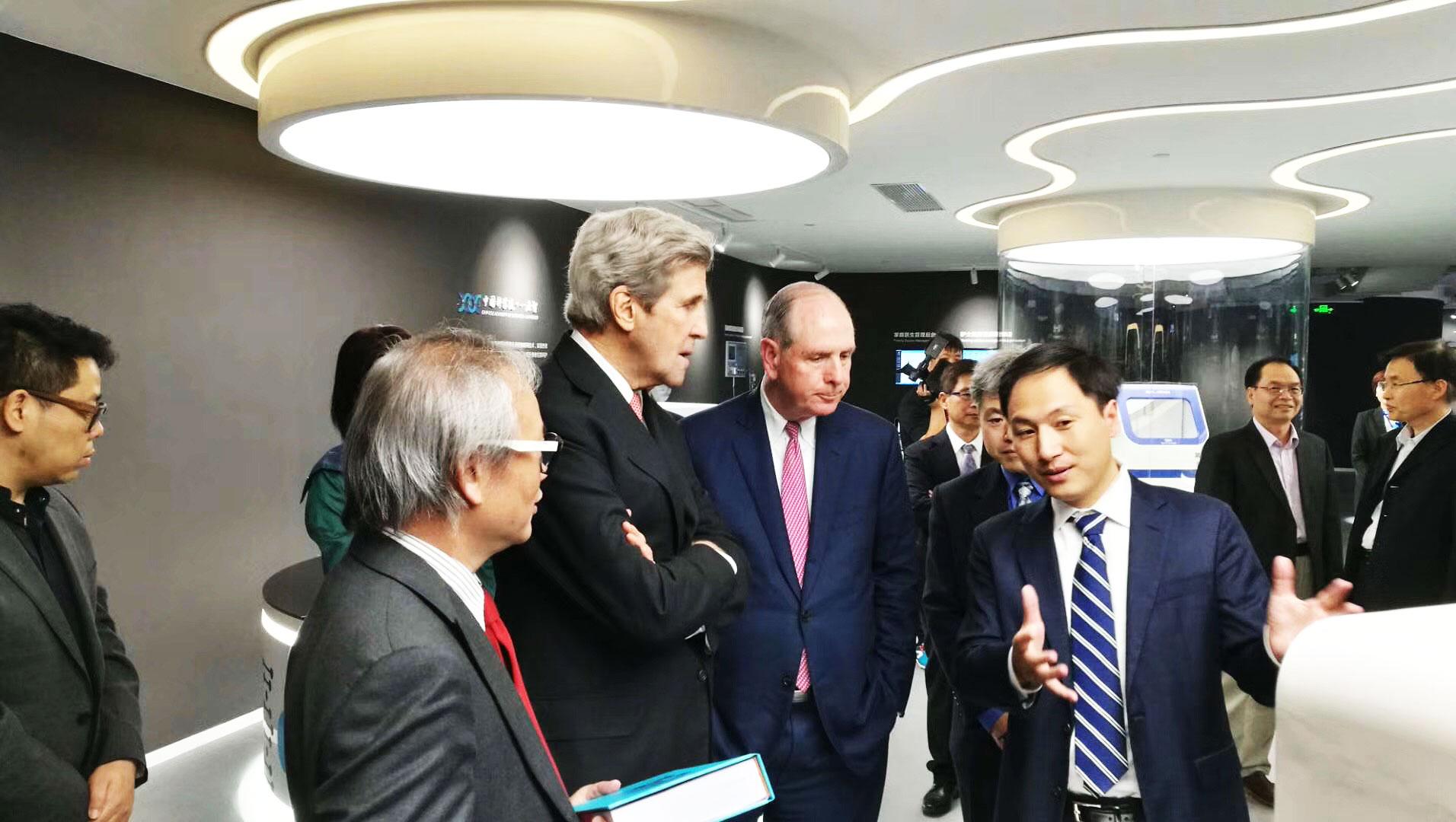 Él Jiankui explica el secuenciador del genoma construido por una de sus compañías, Direct Genomics, al ex secretario de estado estadounidense John Kerry.