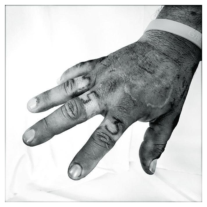 La mano de Jorge Alberto lleva tatuajes relacionados con pandillas.