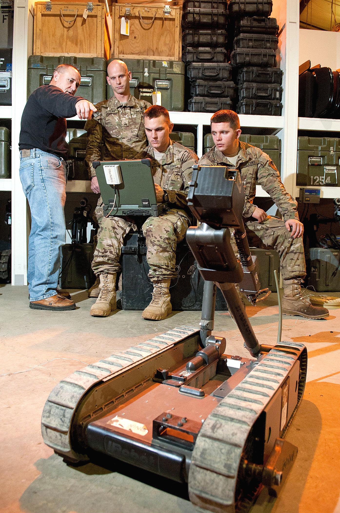 Un entrenador civil muestra a los paracaidistas cómo configurar la pantalla para un robot de campo de batalla PackBot. Tan inexpresivos como pueden parecer estos robots, los soldados en el campo desarrollan vínculos con ellos, viéndolos como parte del equipo.