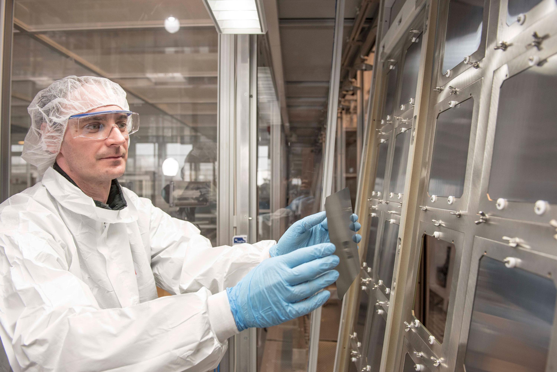 Un trabajador de Oxford PV examina las células solares en tándem de silicio de perovskita de tamaño comercial.