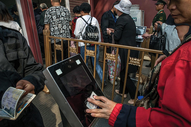 Los visitantes de la Plaza Tiananmen en Beijing escanean sus identificaciones en un puesto de control.