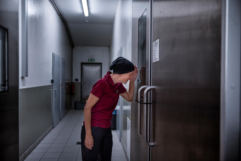Después de bañarse, lavarse el cabello y ponerse ropa estéril, Kessler se asoma a una habitación que alberga a los cerdos de investigación.