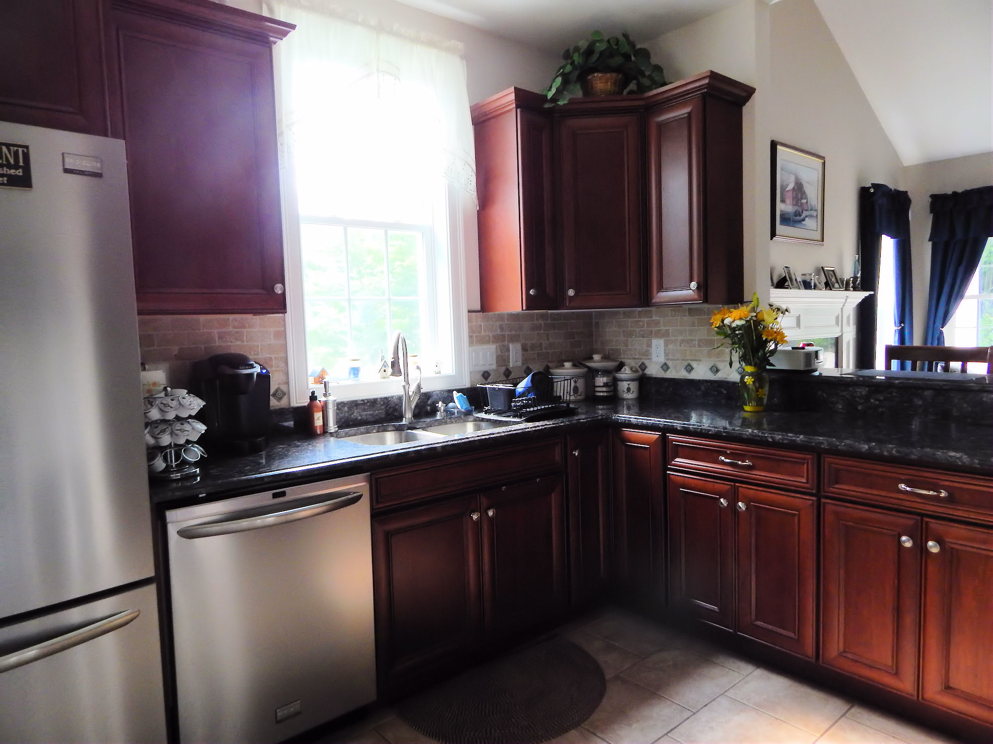 Kitchen with stainless appliances, cherry cabinets, tile floors