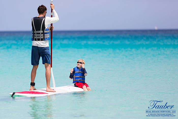 Man paddle boarding with child on the ocean in Jupiter Beach, Florida