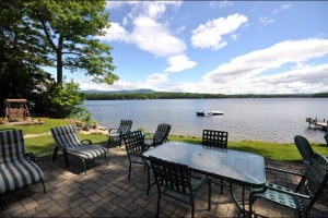Lakeside patio at Deerhaven is one of several sitting areas on this 5.38 acres parcel. Casual luxury and privacy are outstanding features of this NH lake property
