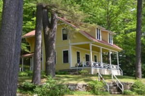 This Winnipesaukee classic cottage was designed with 5 upstairs bedrooms, including maids's quarters. A vaulted Living Room with fireplace below opens to a West-facing porch.