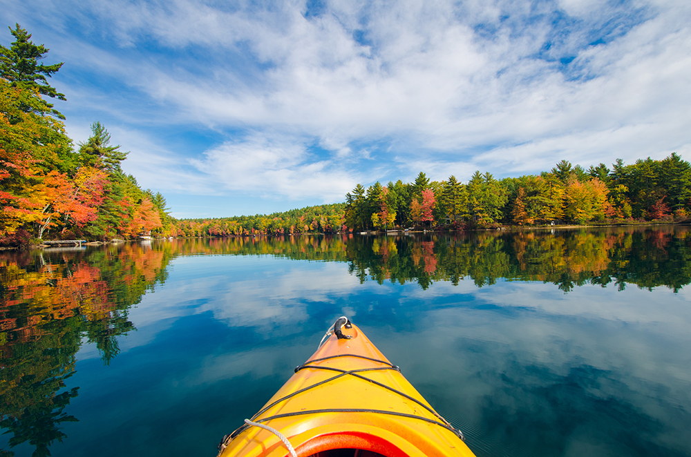 Yellow canoe on Sebago Lake with fall foliage and blue skies