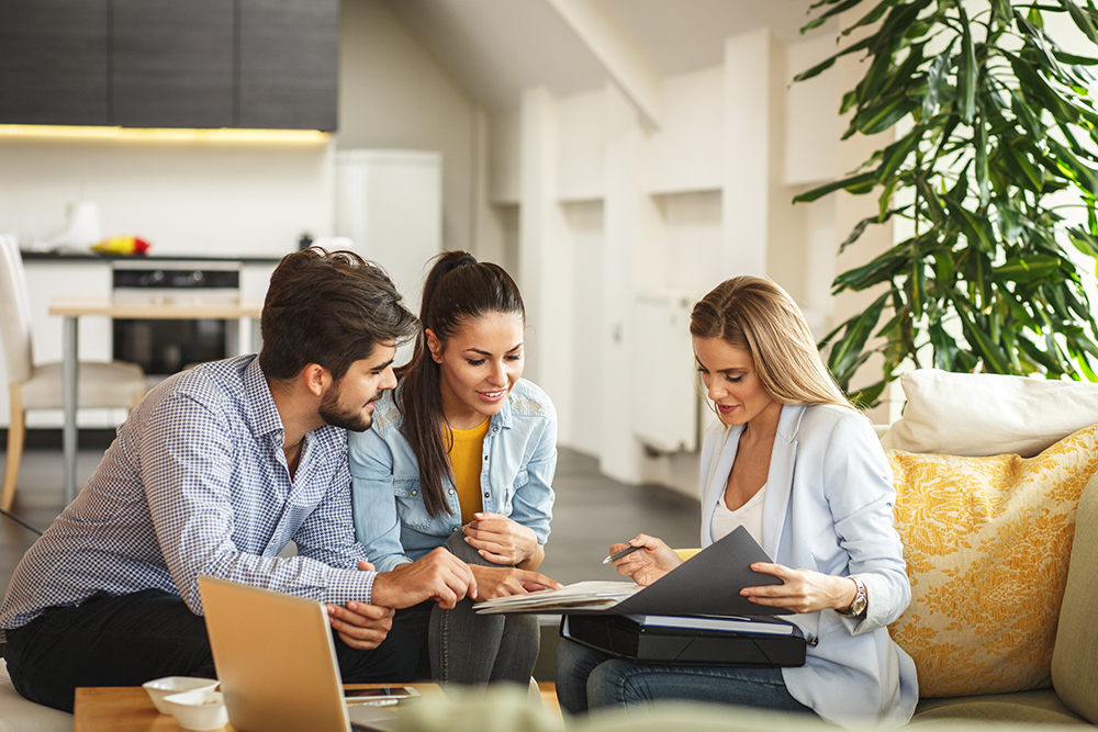 A couple meeting with a realtor inside a house
