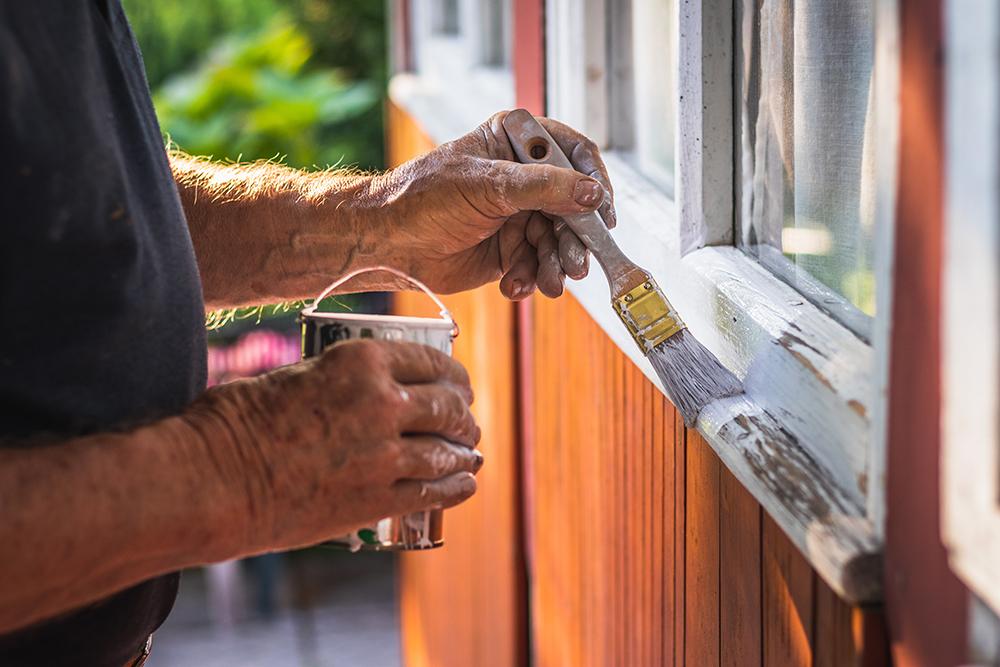 Man painting cabin window
