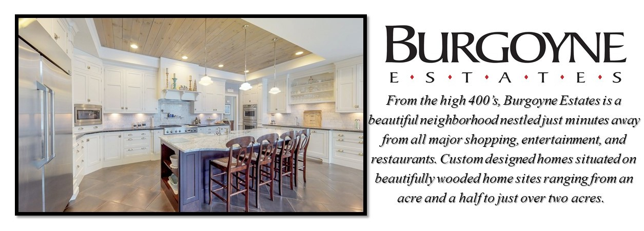 Large, Open Kitchen with White Cabinets and Black Counters, an Island that has Cherry Cabinets and a White Countertop, Stainless Steel Appliances. Burgoyne Estates Neighborhood Logo with description of the community