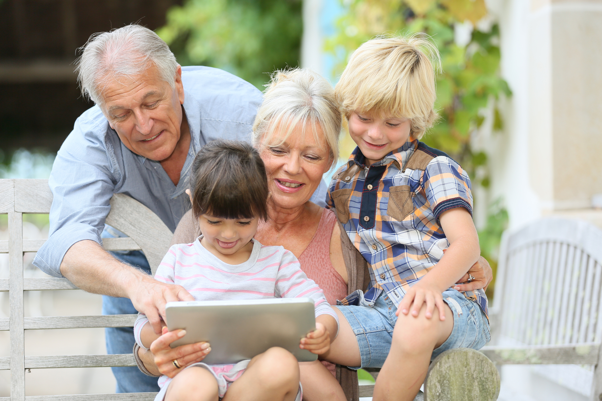 Grandparents with their Granddaughter and Grandson looking at a Tablet