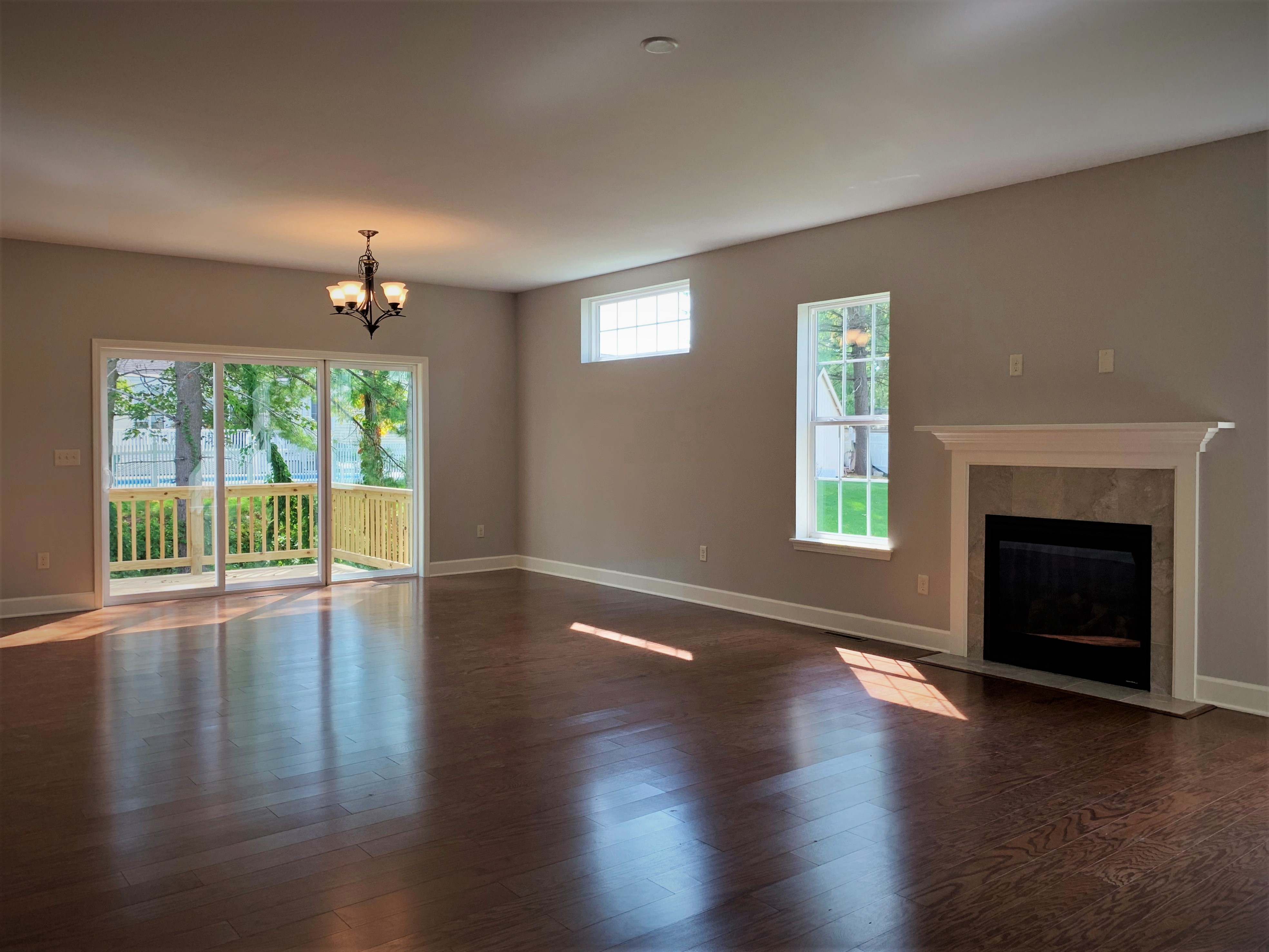Dining/Great Room area with Triple Slider Door, Hardwood Floors and Gas Fireplace with Tile Surround and White Mantel