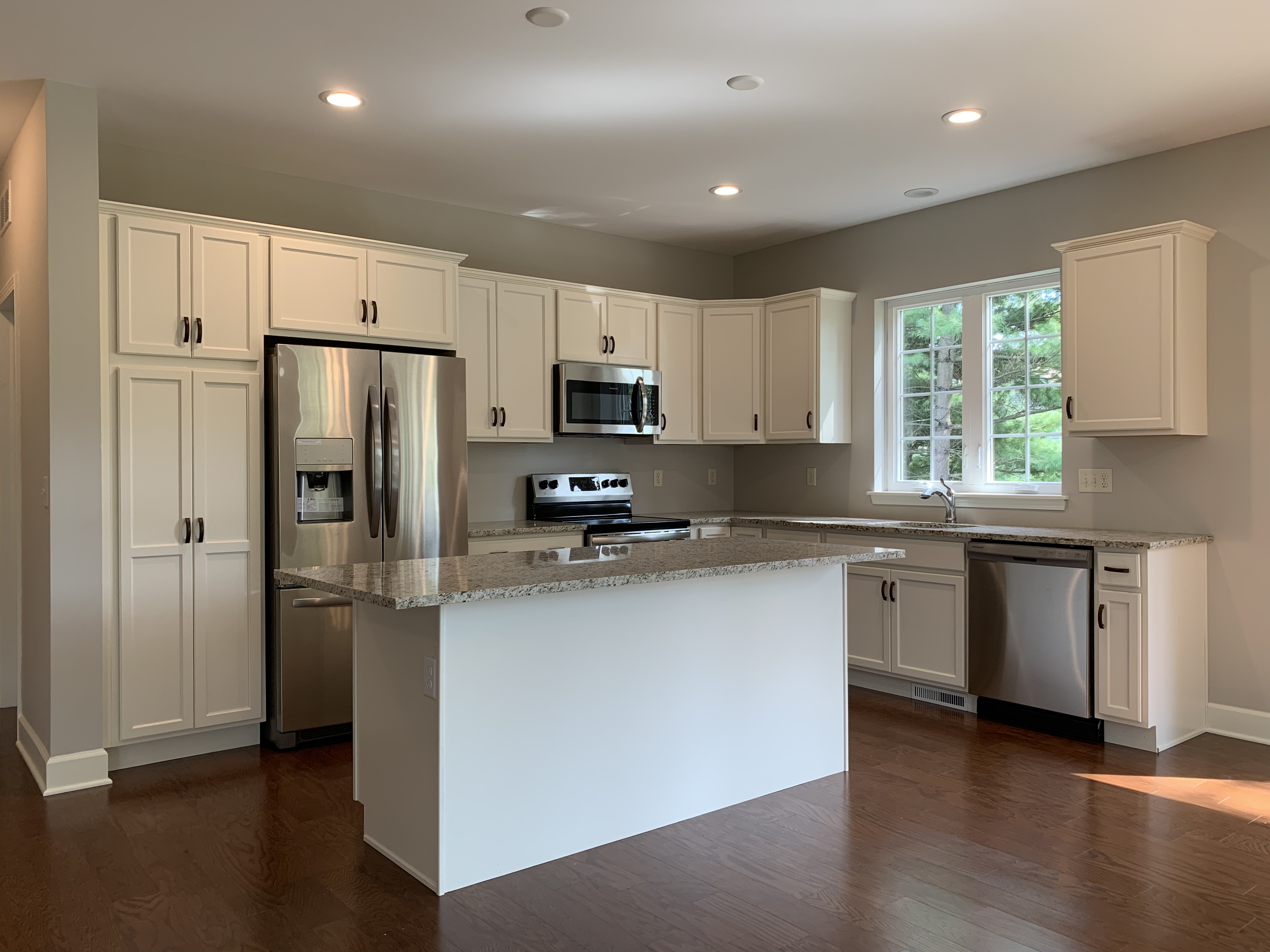 Kitchen with Hardwood, White Cabinets, Granite Counters and Stainless Steal Appliances