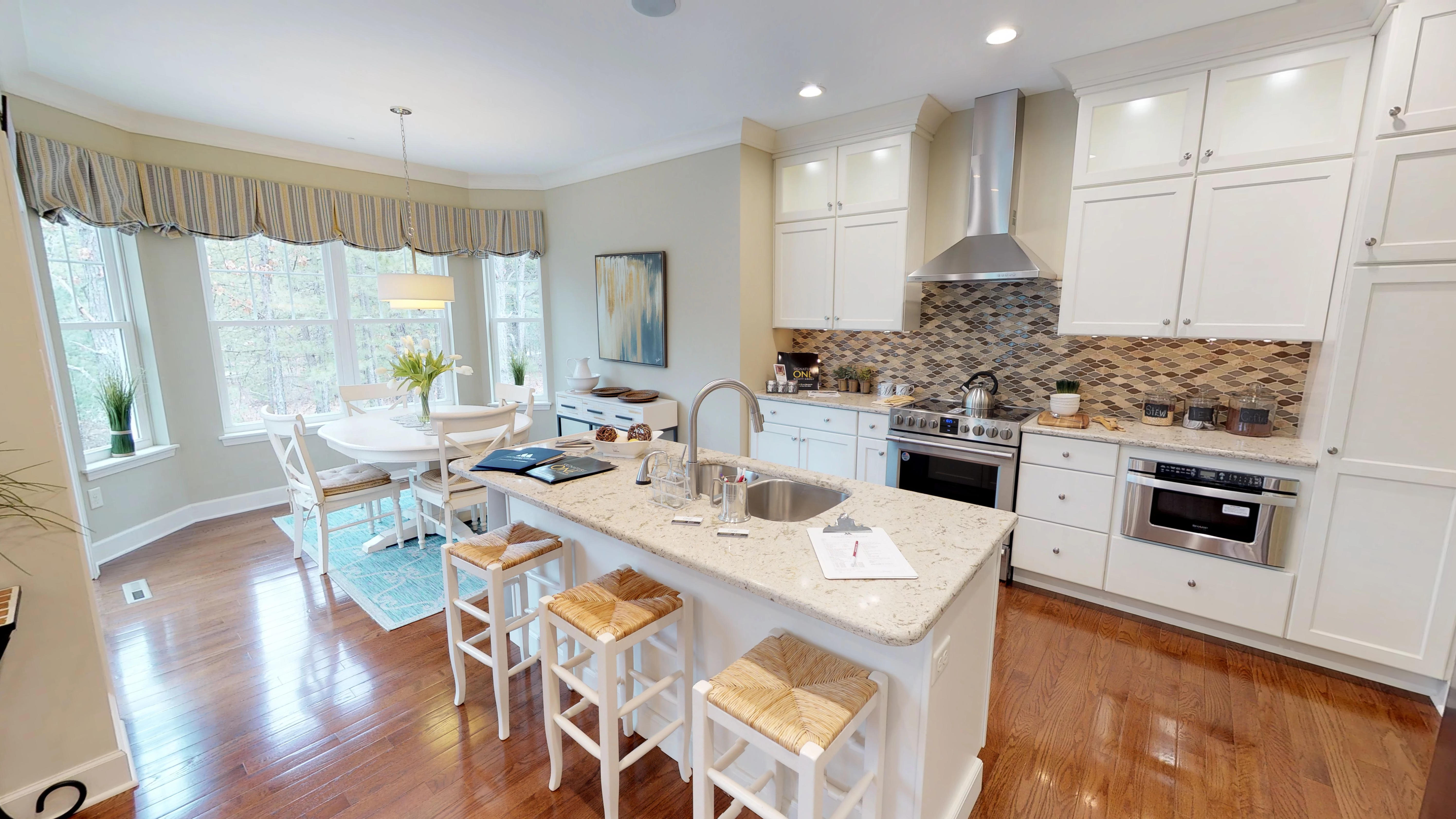 Kitchen and Dining area with an island, white cabinets, quartz counters and hardwood floors