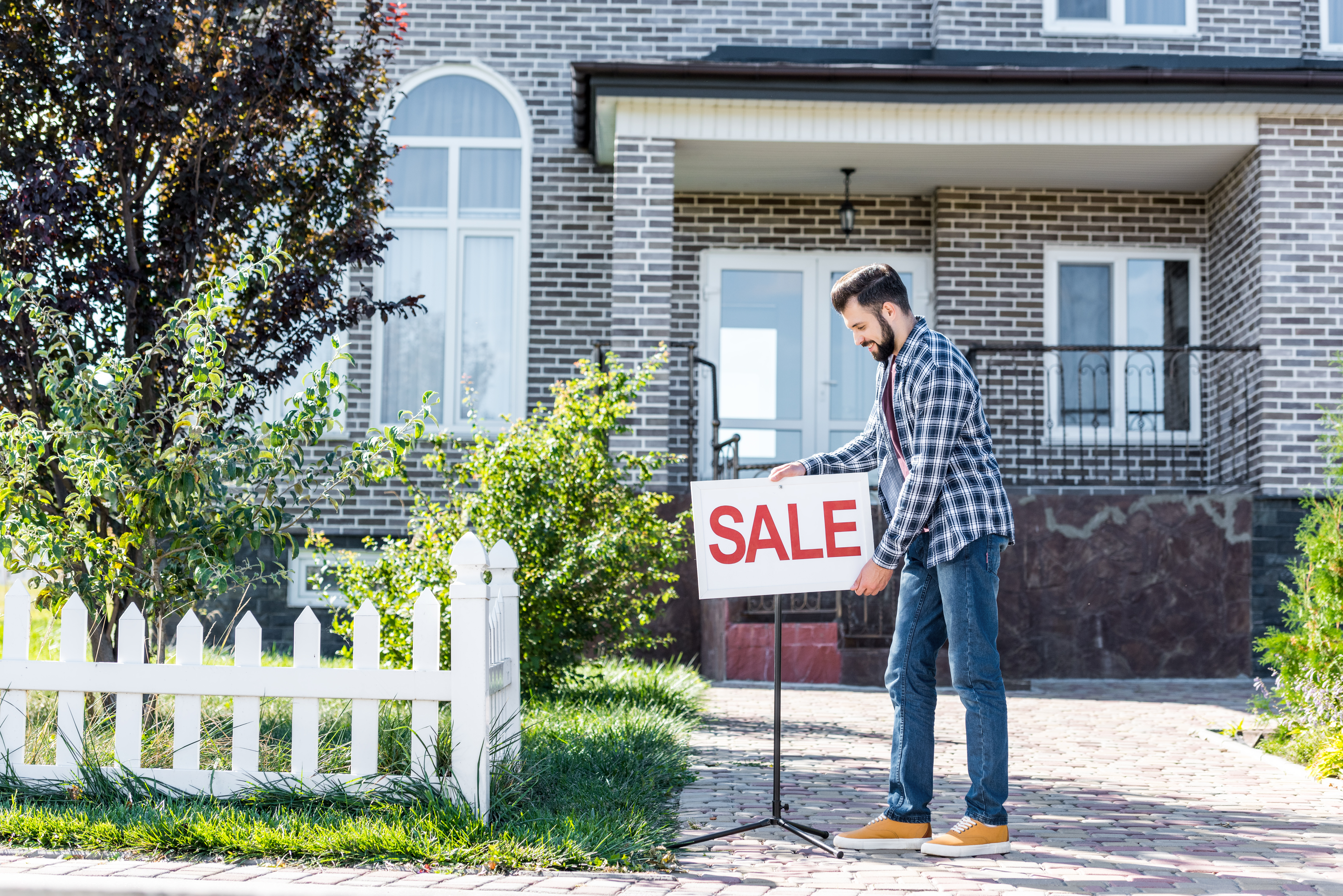 A home seller placing a SALE sign on their property