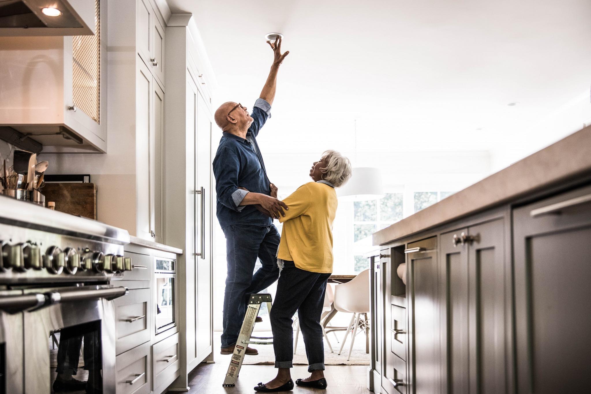 man and woman installing light bulb