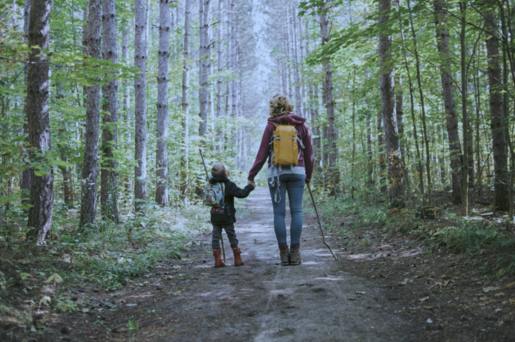 woman walking with child in woods
