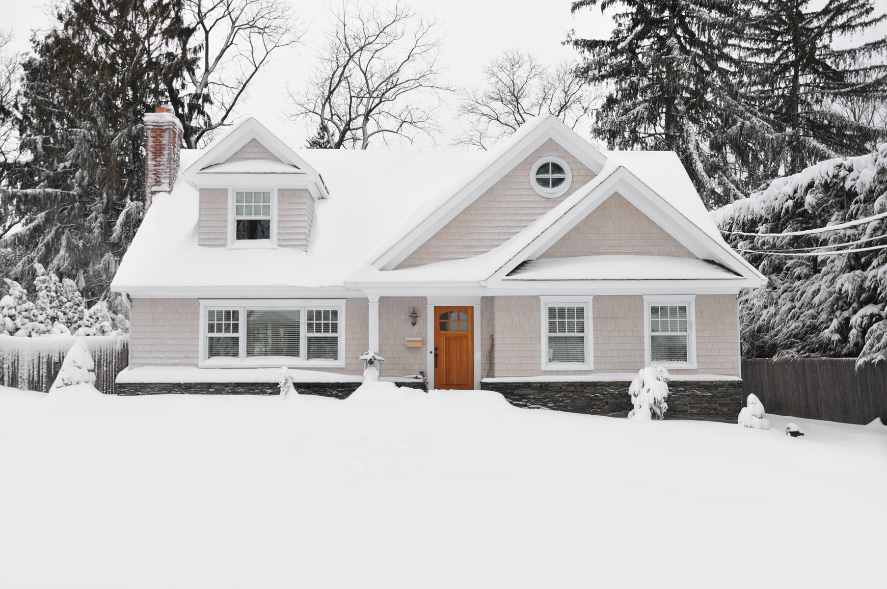 house and snow covered yard trees