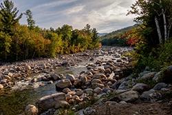 A riverside image of a rocky river bed surrounded by trees in Enfield, NH