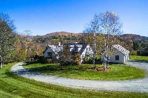 A secluded single-family home surrounded by trees with a round driveway, located in the Upper Valley.