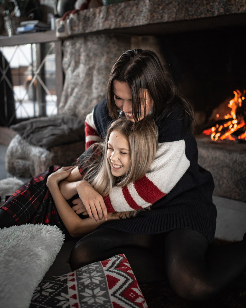 two children laughing by the fireplace