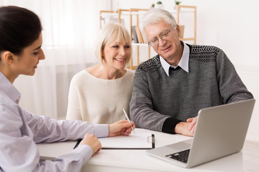older couple with computer and real estate agent
