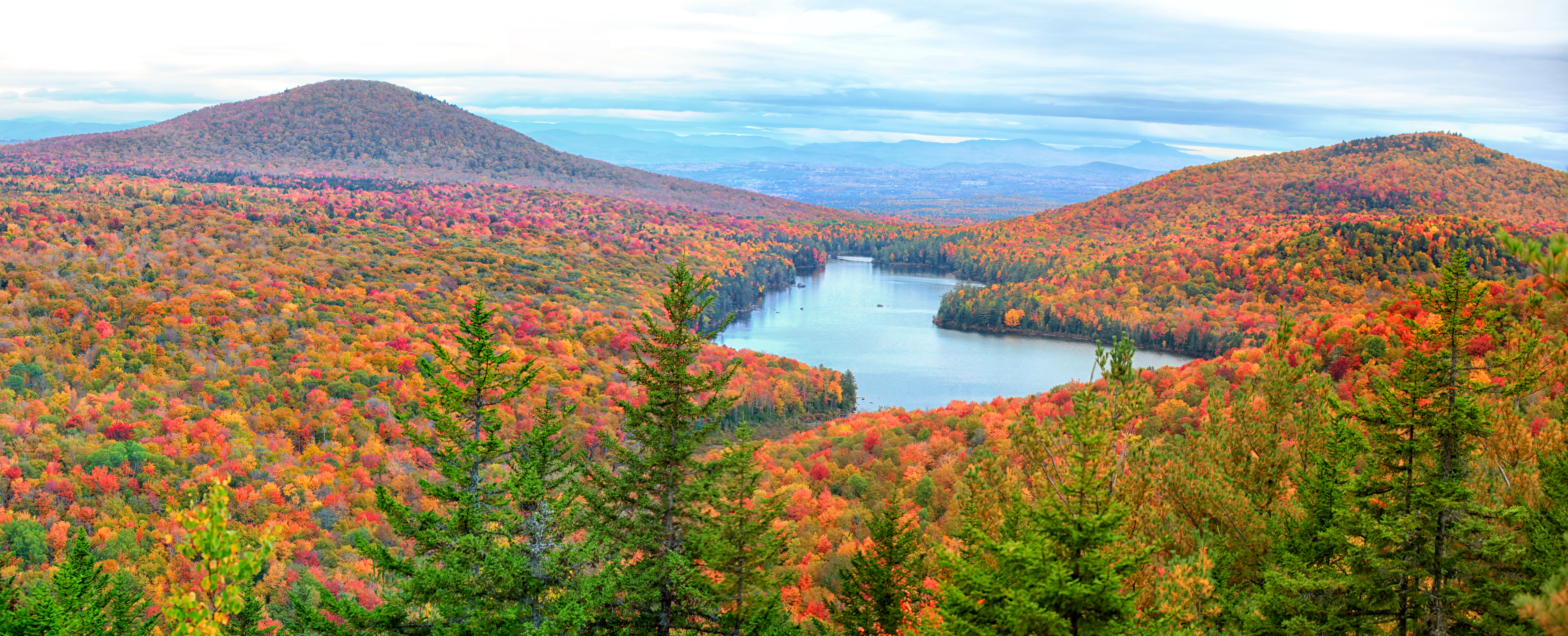 A scenic view of rolling mountains during peak foliage in Essex, Vermont