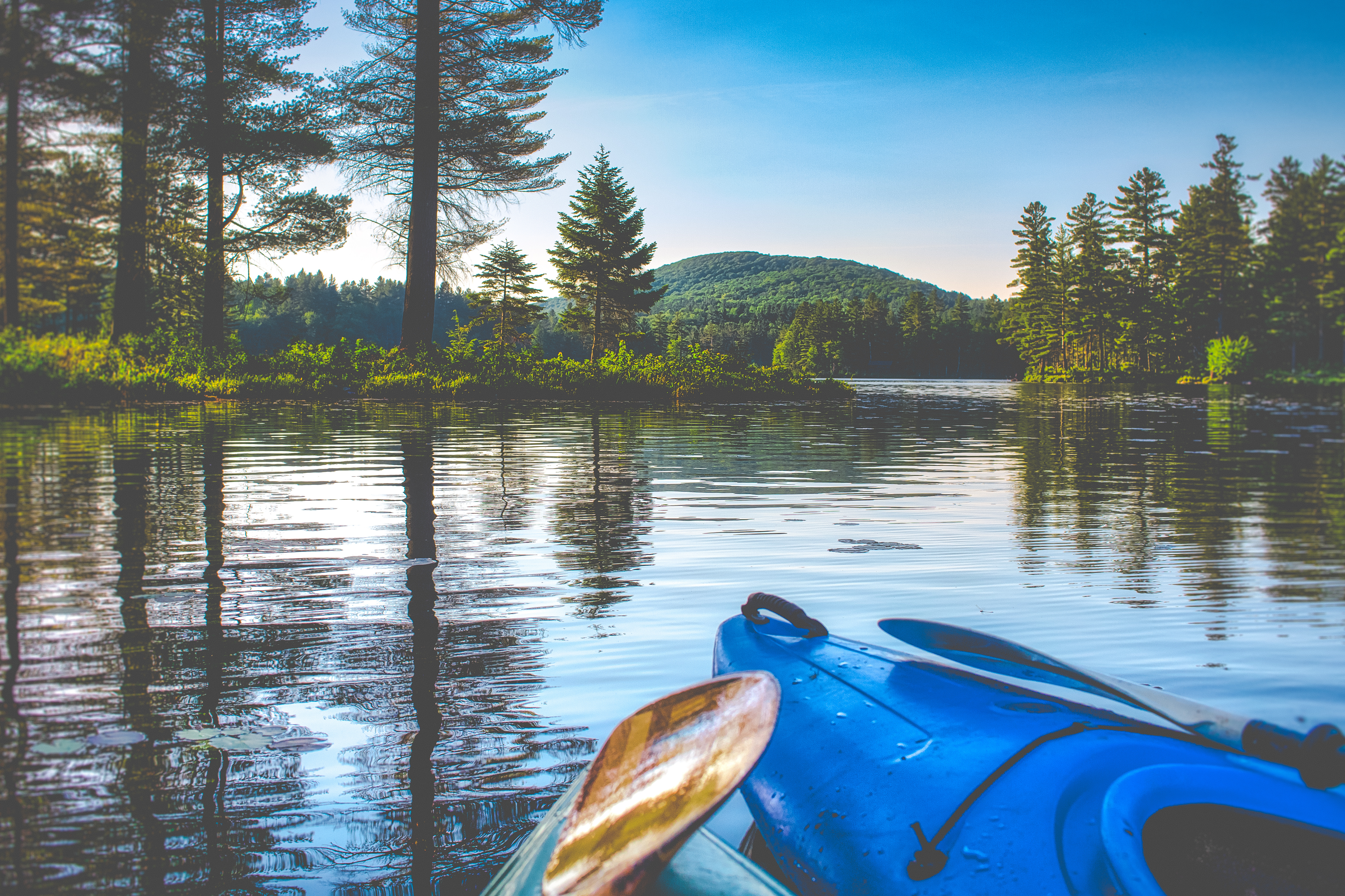 A scenic view of surrounding mountains and woods as shown by a kayak in th ewater