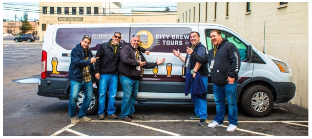 The crew form City Bew Tours points at their tour van