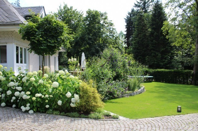 using a wide border garden to transition between an outdoor dining area and the rest of the yard
