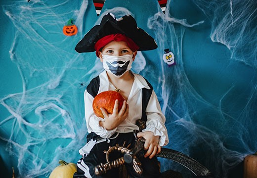 A picture of a young boy holding a pumpkin, wearing a pirate hat and a mask decorated with a beard