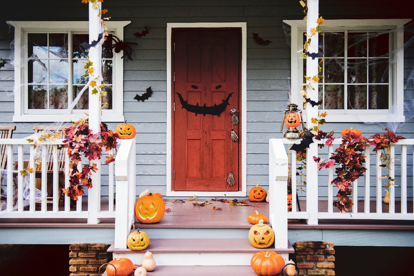 Porch decorated with pumpkins, paper bats