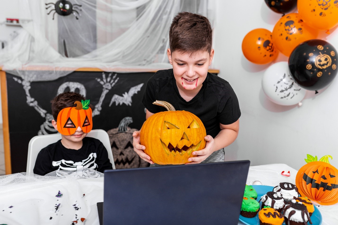 A boy with a laptop, smiling. Halloween decorations behind him.