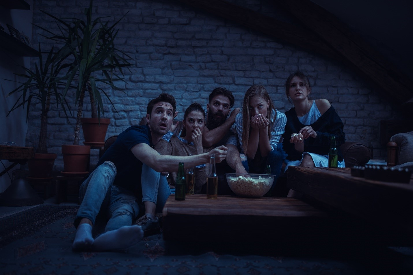 A group of people on a couch watching television and looking frightened