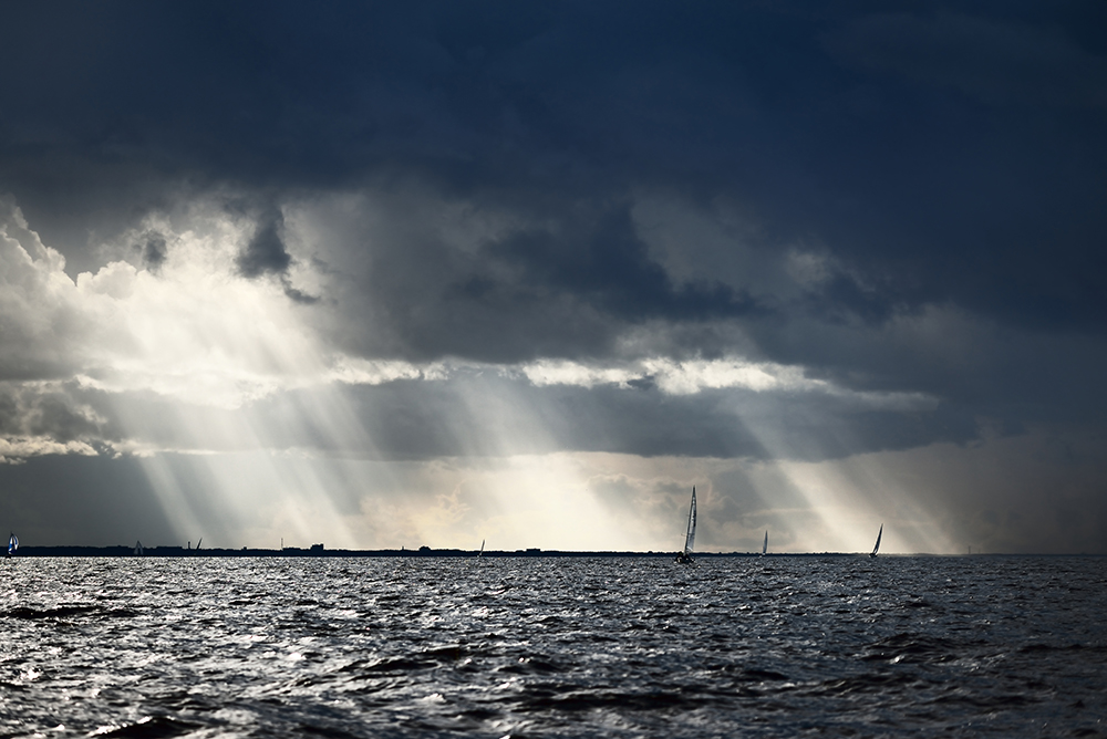 Boats on the Ocean with a Grey Sky and Sunrays Poking Through