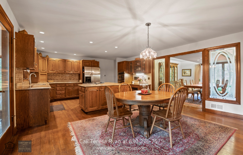 Winfield, IL home - The kitchen features its own eating area and island with a built-in cooktop and grill.