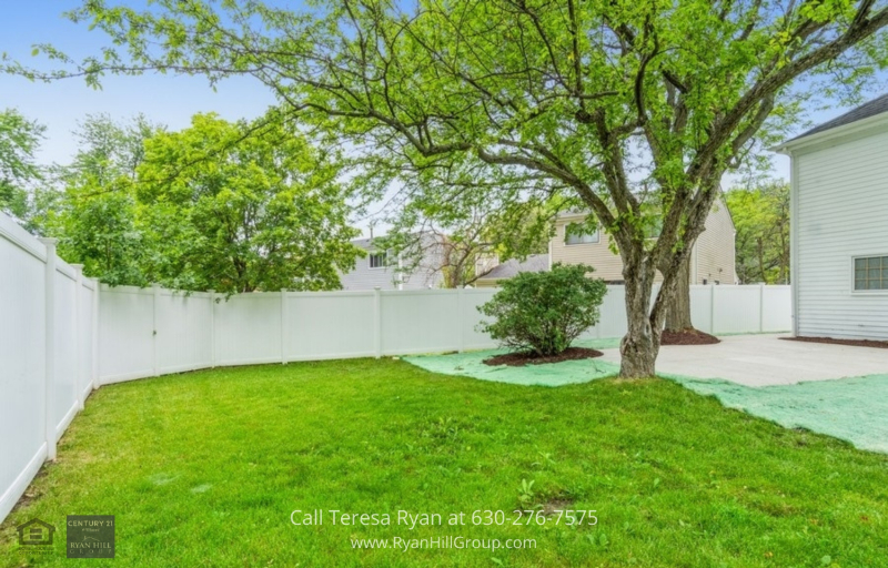 Aurora IL Real Estate Properties for Sale - The large, white-fenced backyard of this Aurora IL home has mature trees and all the room you need to create a wonderful garden.