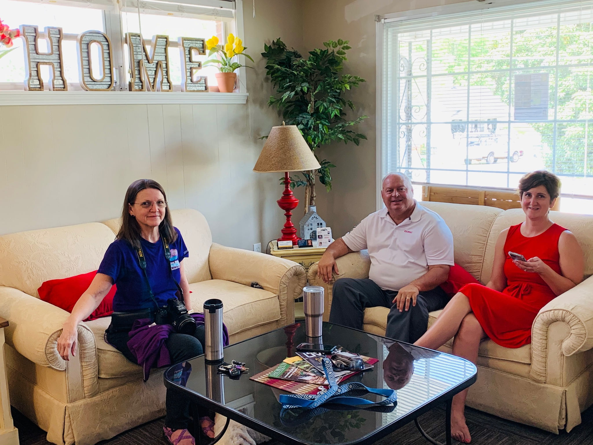 Small town service and a feeling of home as photographer and Plum Branch Yacht Club owner Bea McClain visits with RE/MAX Leisurely Living owners Cara and Russ in the lobby of their new building on E. Gold St.