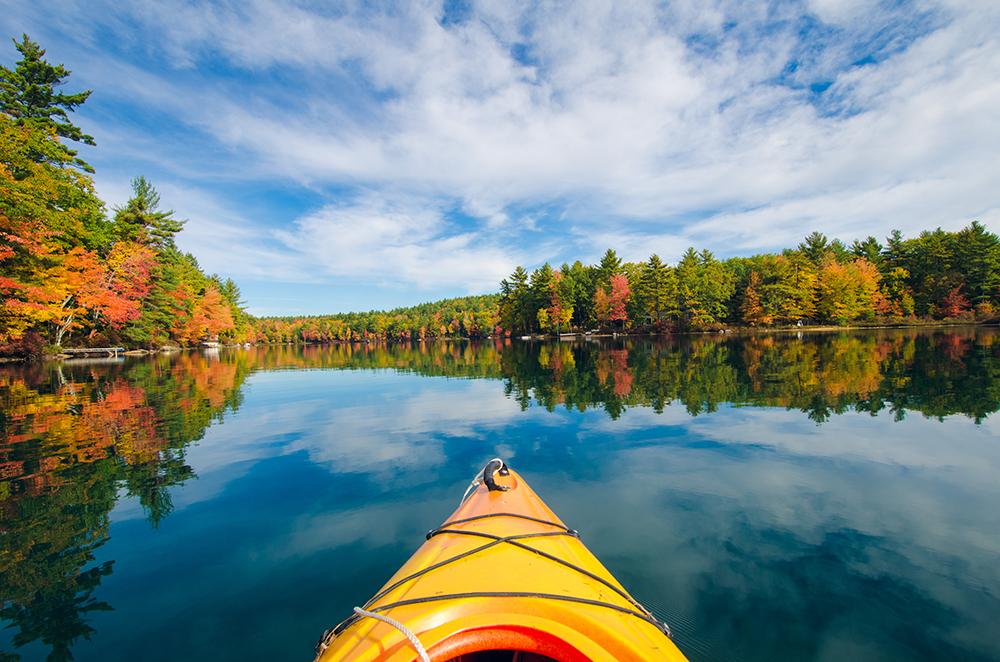Yellow canoe on Sebago Lake with fall foliage and blue skies