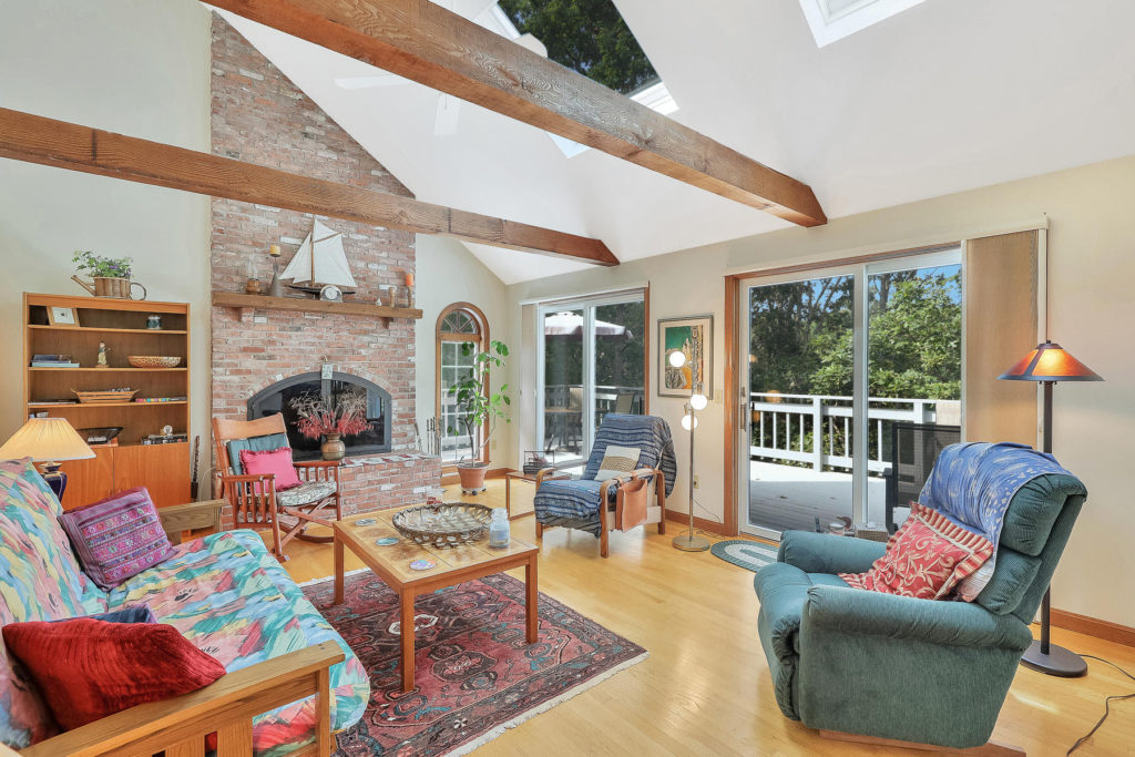 Brick fireplace and beamed ceilings in living room