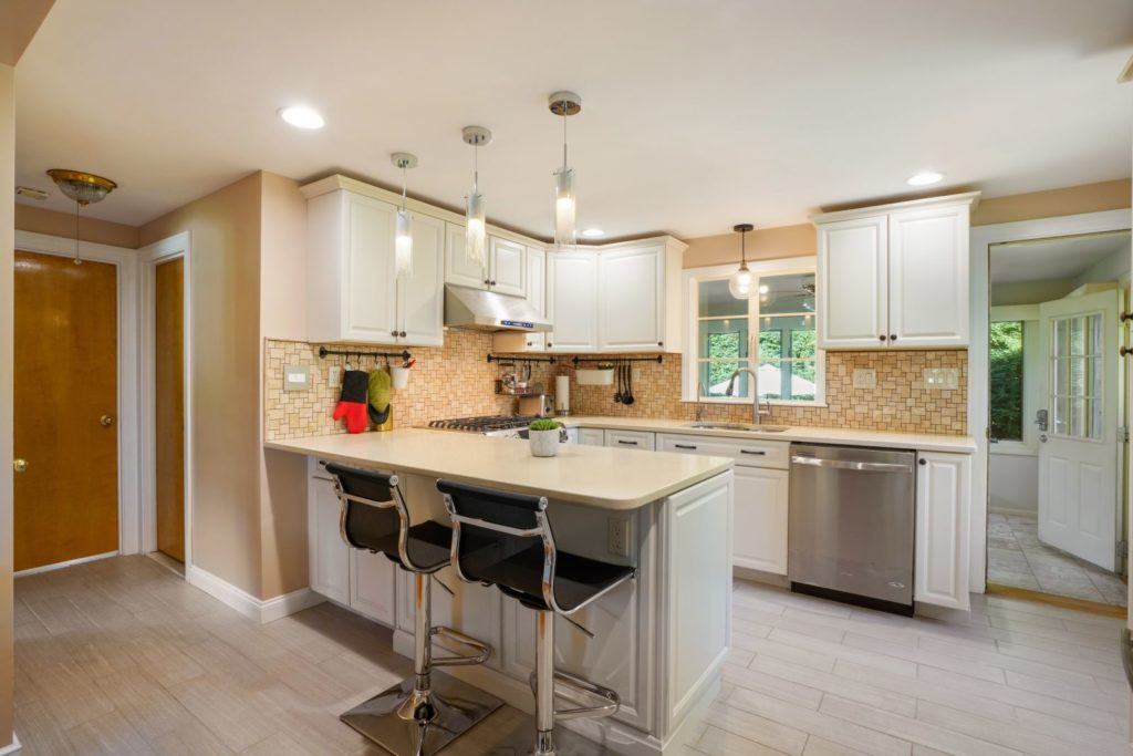 Tan kitchen with island and two stools