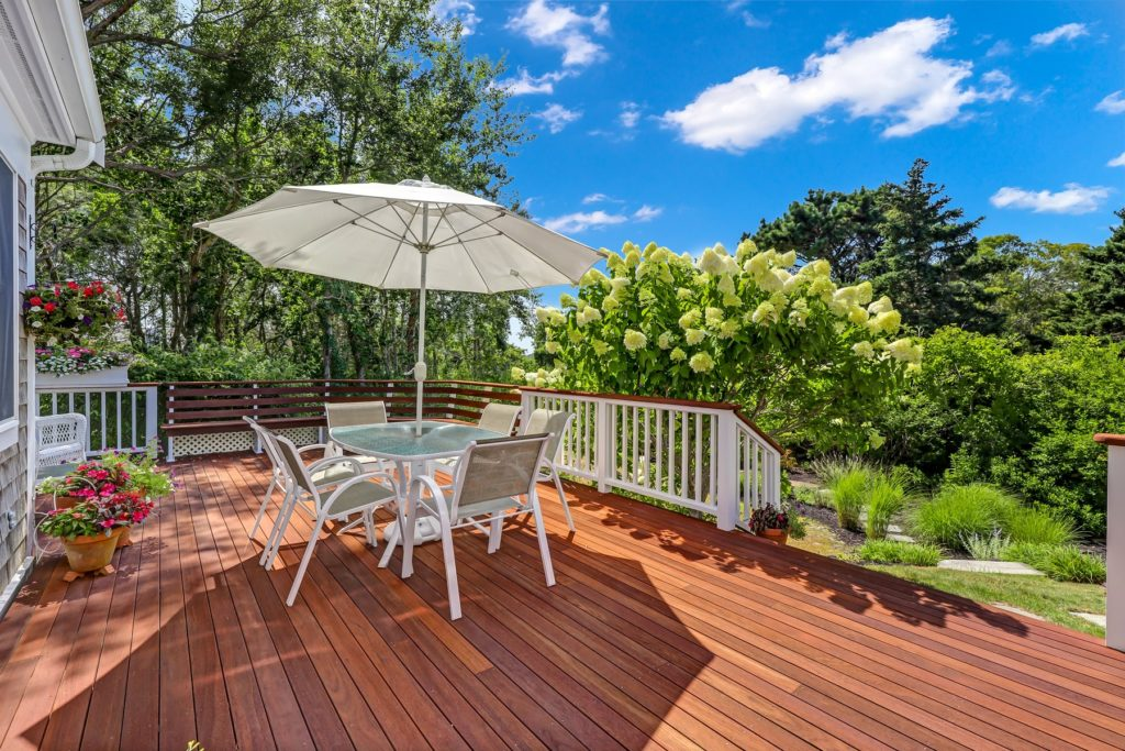 Deck with table and umbrella overlooking backyard