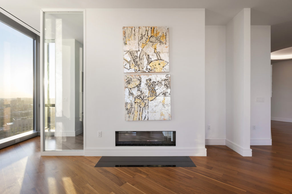Open concept living room with wall art over fireplace